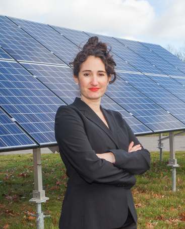 Jenny Rushlow standing in front of solar panels
