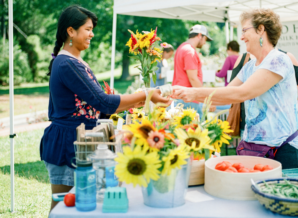 Eva Moss (left) sells flowers at a farmers market in North Carolina.