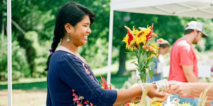 Eva Moss sells flowers at a farmers market.